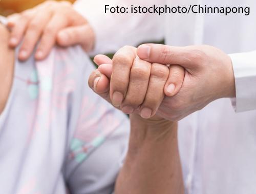 Ein Pfleger hält die Hand eines Patienten.