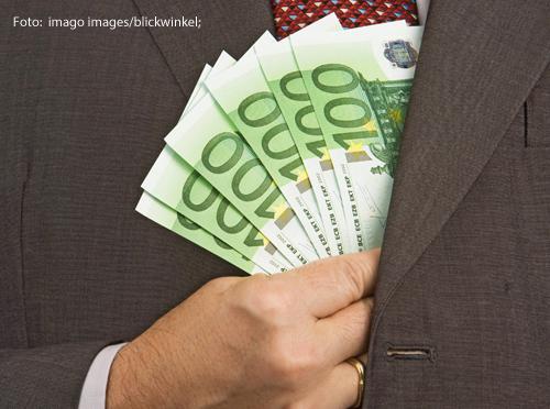 Ein Mann steckt 100-Euro-Scheine in seinen Anzug