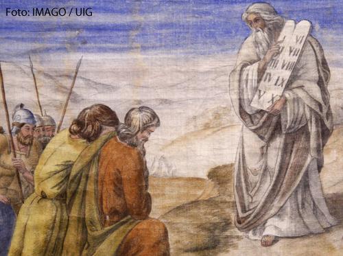 Ein Bild zeigt Mose, der die Zehn Gebote auf Steintafeln in der Hand hält.