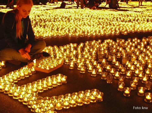 Ein Mädchen sitzt in mitten hunderter brennender Kerzen.