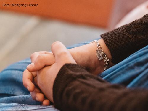 Eine Frau hat ihre Hände zum Gebet gefaltet.