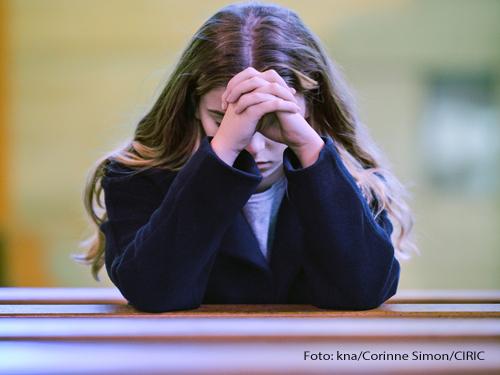 Eine Frau betet in der Kirche. Foto: kna/Corinne Simon/CIRIC