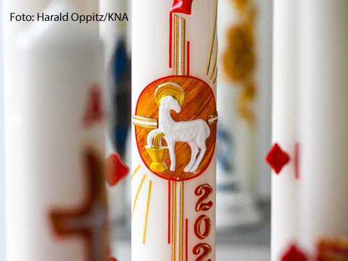 Eine Osterkerze ist mit einem Lamm verziert und steht auf einem Tisch eines Kerzenherstellers in Köln.
